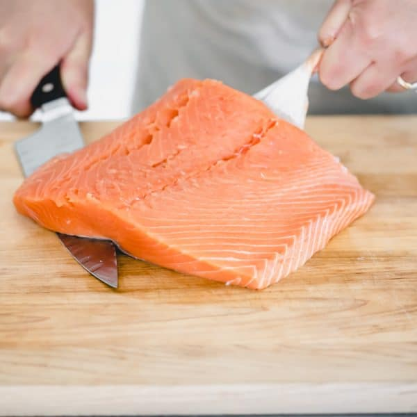 slide the knife under the salmon flesh and pull back on the skin
