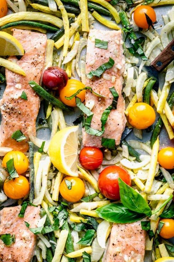 a close up of roasted salmon with basil and cherry tomatoes