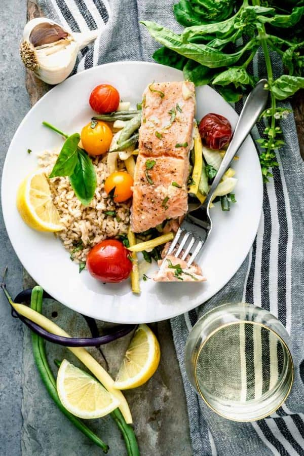 A plate with roasted salmon, green beans and cherry tomatoes and brown rice