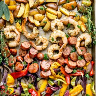 a close up of shrimp and sausage on a sheet pan with peppers and onion