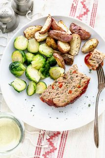 a plate with a slice of turkey meatloaf with potatoes and brussels sprouts