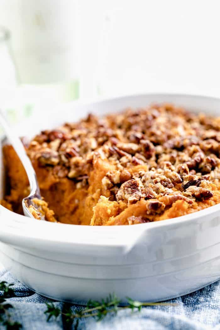 A close up side view of sweet potato casserole with pecans on top