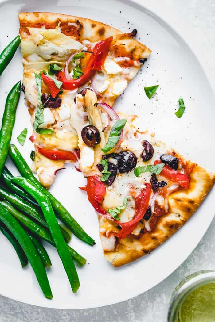 Greek Pizza slices on a plate with green beans