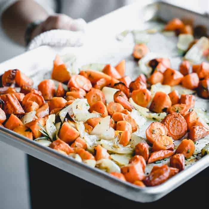 A close up of a sheet pan of roasted carrots and onions