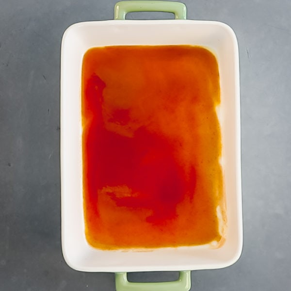 spread 1/2 cup enchilada sauce in casserole dish