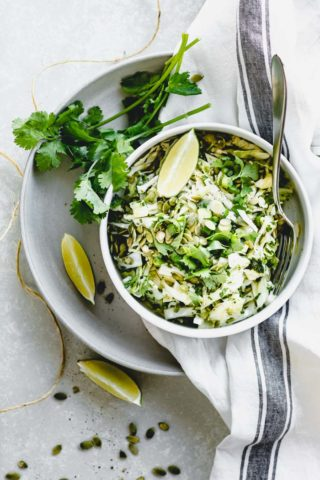Coleslaw overhead in a single bowl with lime wedges and cilantro