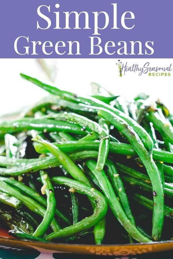 Close up of green beans on an orange platter with text overlay saying simple green beans