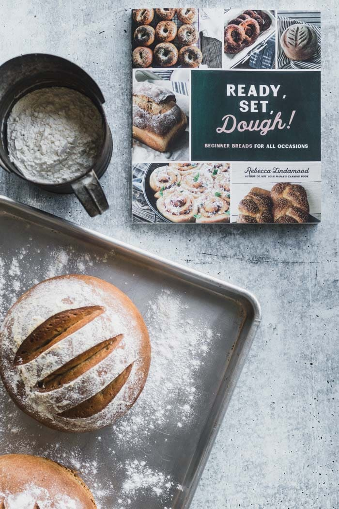 Loaf of bread on baking sheet next to cookbook