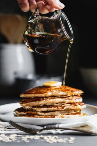 Oatmeal Pancakes with a pitcher or syrup pouring over a stack of pancakes