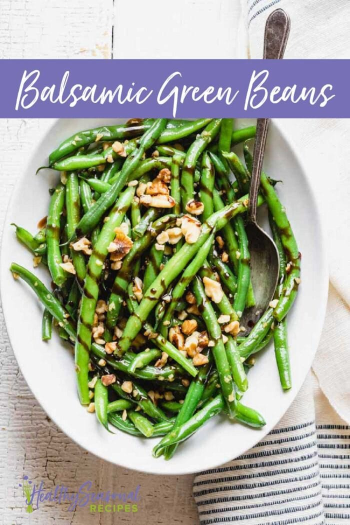 Overhead oval bowl with green beans topped with walnuts and balsamic