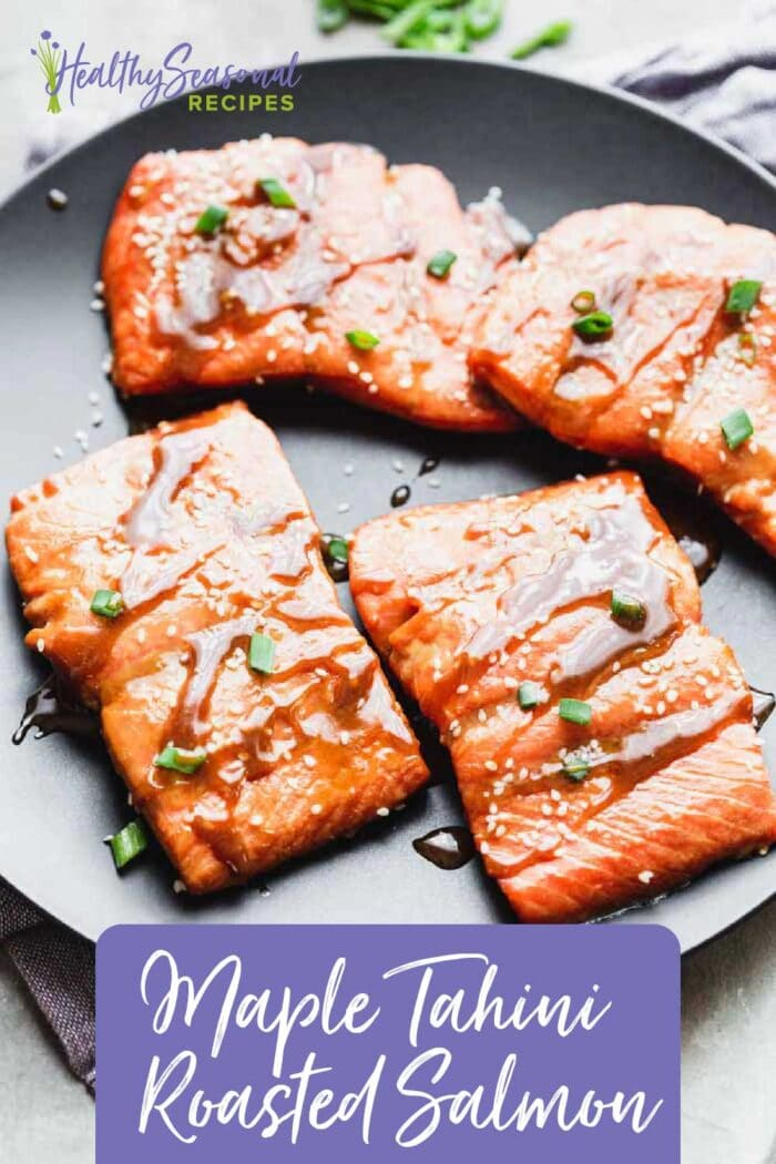 a black plate with salmon filets on top