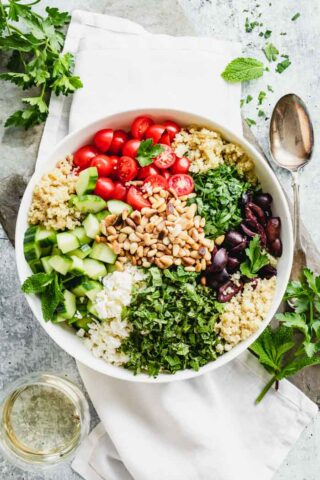 A bowl topped with Mediterranean ingredients