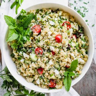 a white bowl with mixed together quinoa salad in it with mint garnish