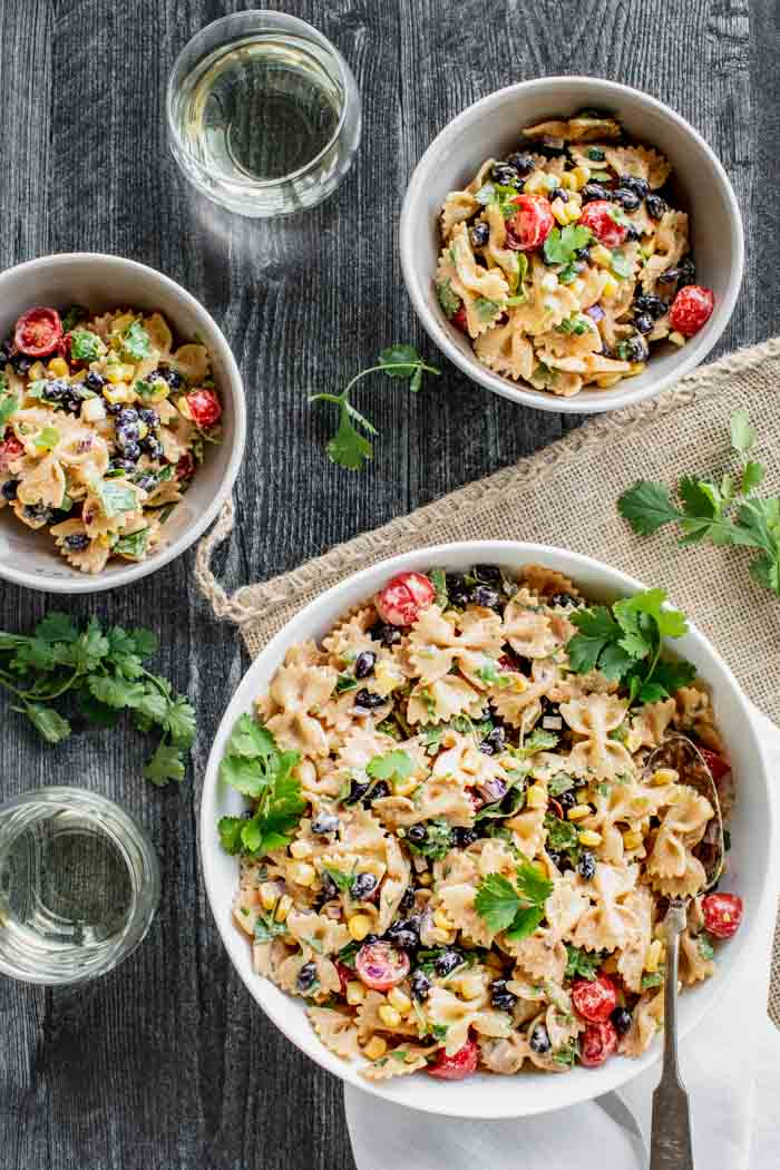 a serving bowl and two servings of Mexican Pasta Salad