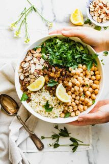 overhead of couscous salad with toppings before stirred together, hands holding bowl