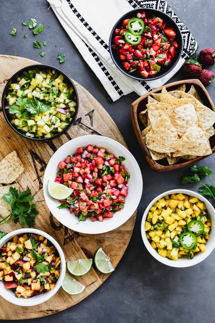 five different fruit salsa on a table with chips and limes