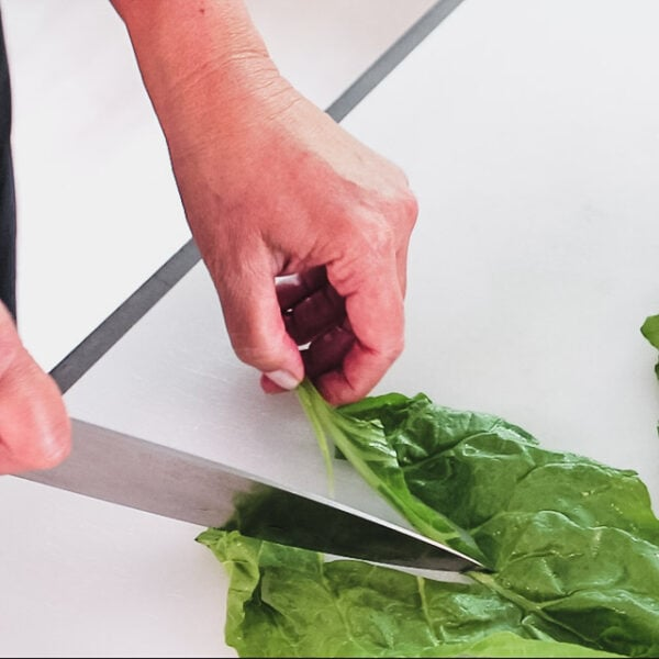 Using a knife to remove stems from chard leaf