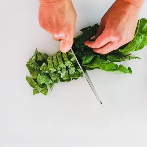 Using a knife to chop chard leaves