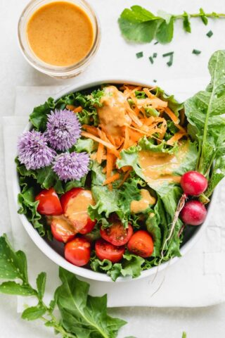 Thai dressing over a salad with chive blossoms