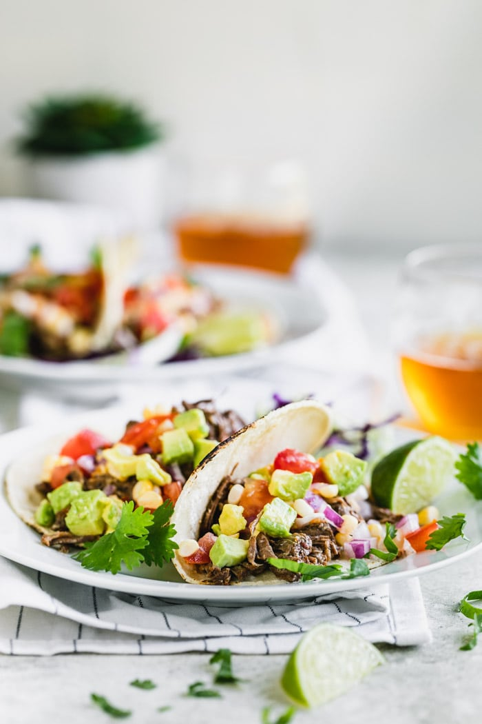 Two beef barbacoa tacos on a white plate in the foreground with another plate of tacos and glasses of beer in the background.