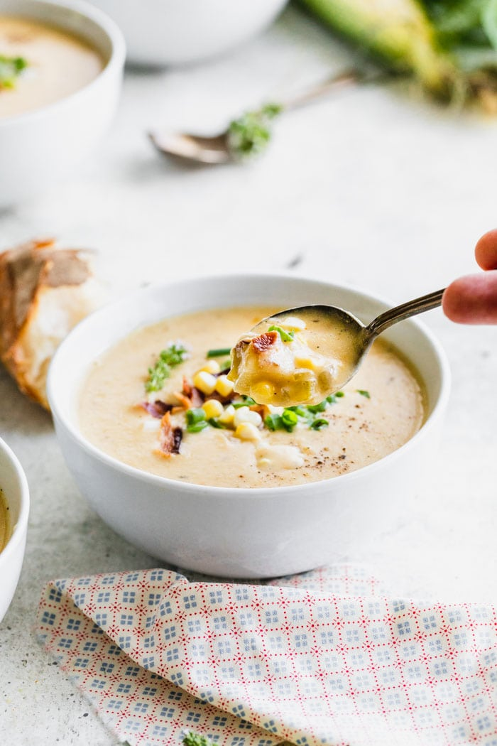 Corn chowder in a bowl with a spoonful held to the camera