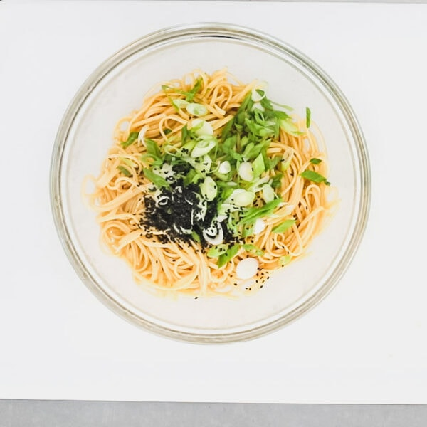 The noodles, scallions and sesame seeds added to the bowl of dressing