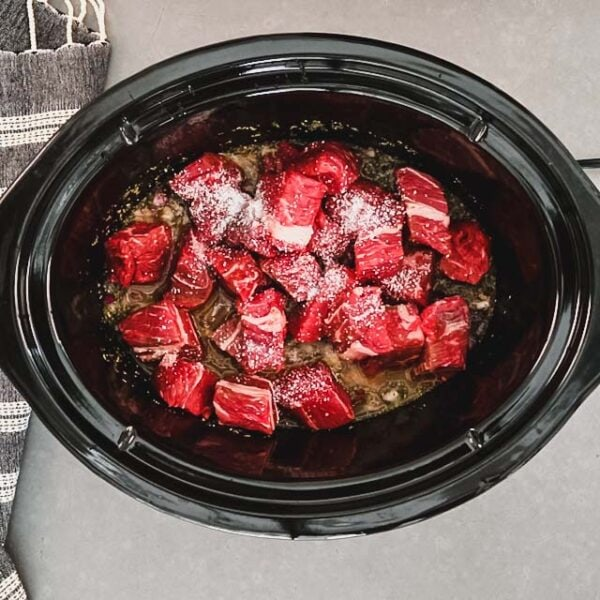 Beef and salt added to mixture in slow cooker.
