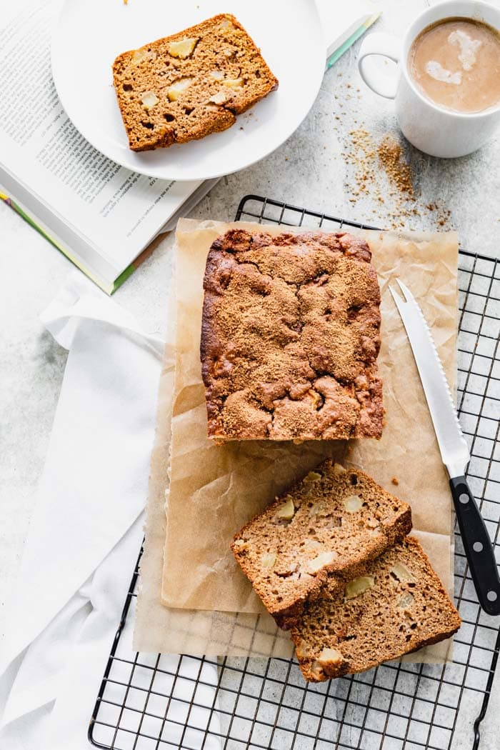 A loaf of apple bread on a cooling rack with a book, a slice of bread on a plate.