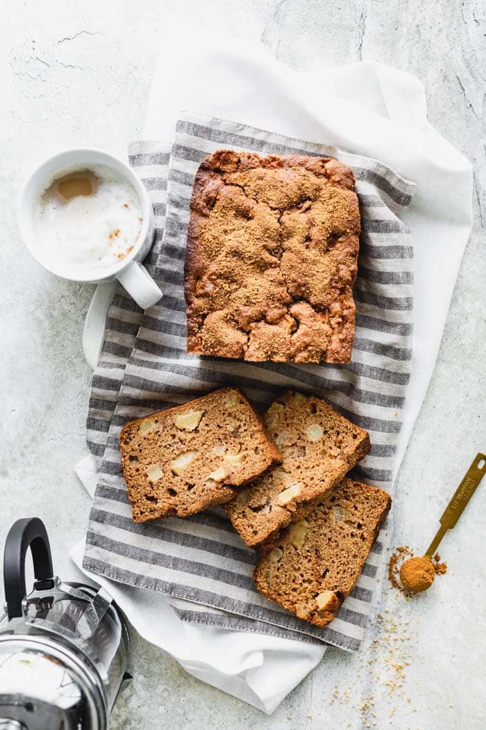 Apple Cinnamon Bread on a striped tea towel with a cup of coffee