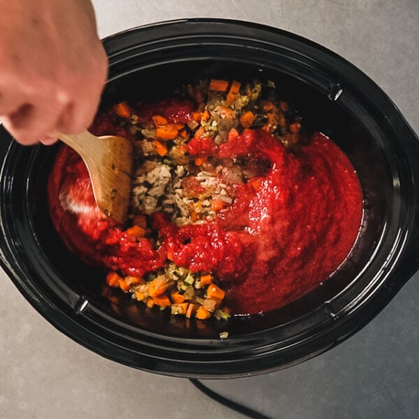 Adding tomatoes and sugar to a slow cooker with turkey and vegetables