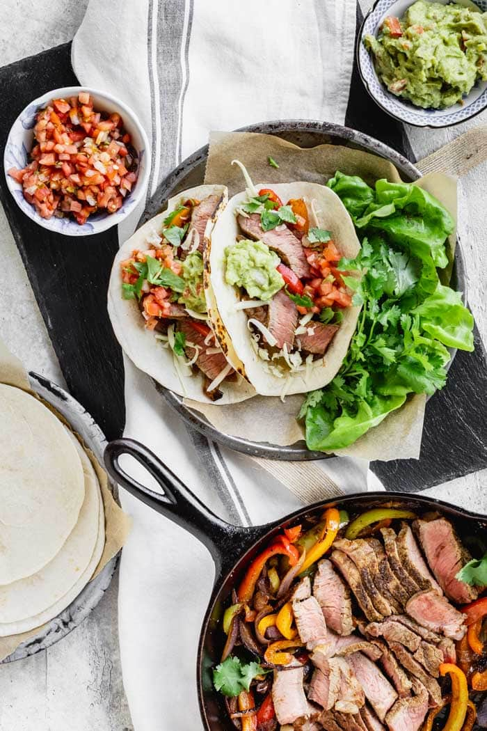 Steak fajitas with a skillet of peppers and steak, a plated serving and some condiments
