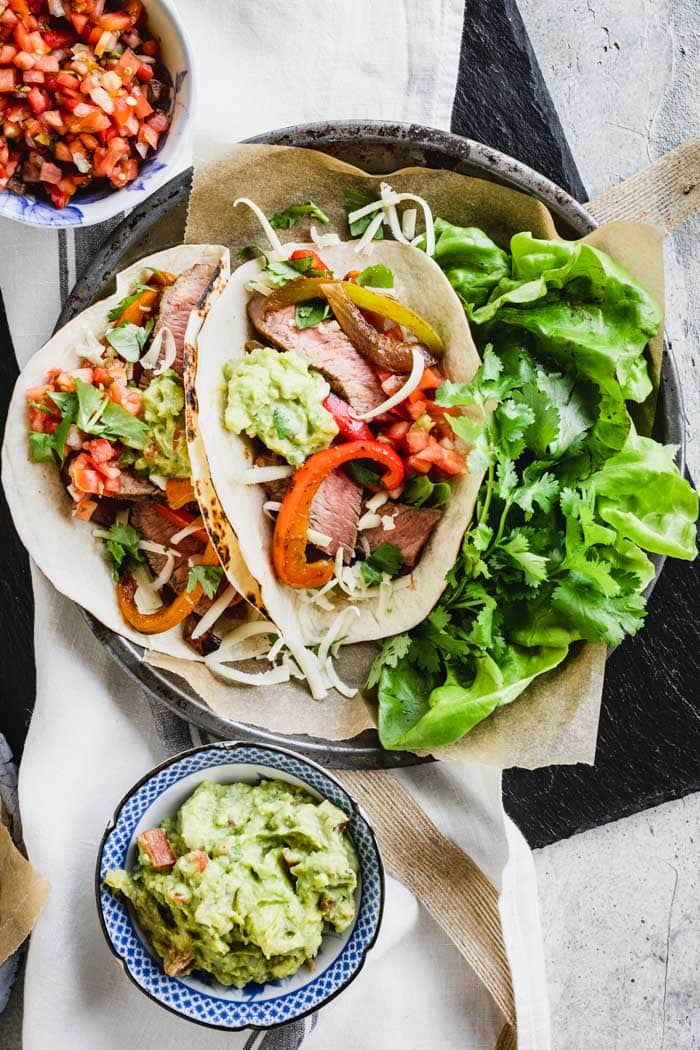 Easy Steak Fajitas in tortillas on a plate with lettuces and cilantro