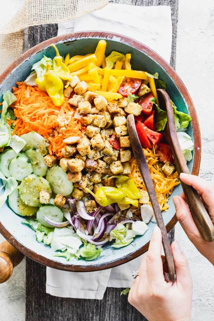overhead of a turquoise painted salad bowl with garden salad in it, two salad tongs and hands on the tongs