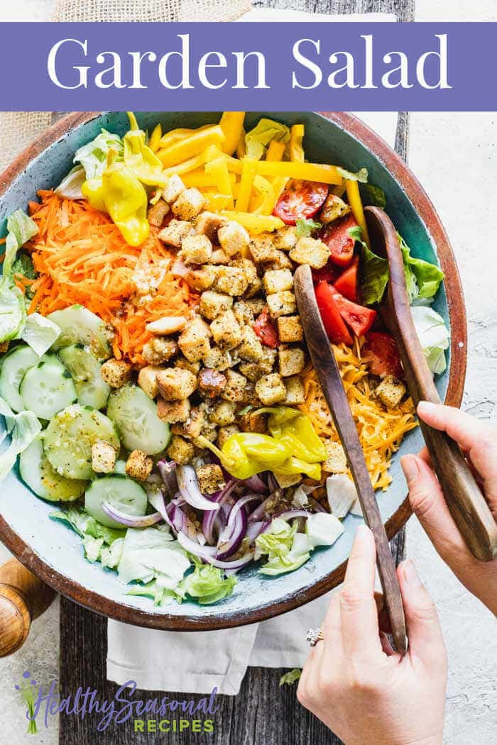 blue bowl with Garden salad in it and a person holding the salad tongs