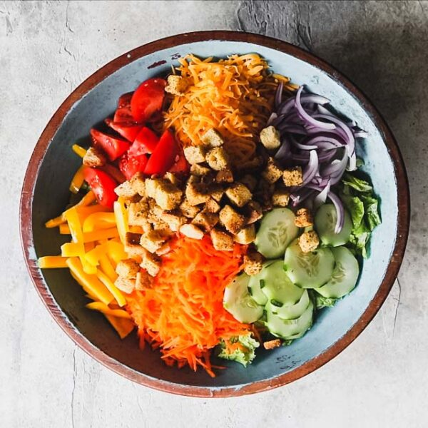 Combine, lettuce, vegetables, cheese and croutons in a large salad bowl.