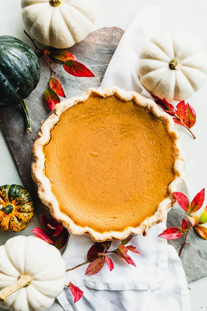 overhead of an uncut pumpkin pie with white pumpkins and fall leaves