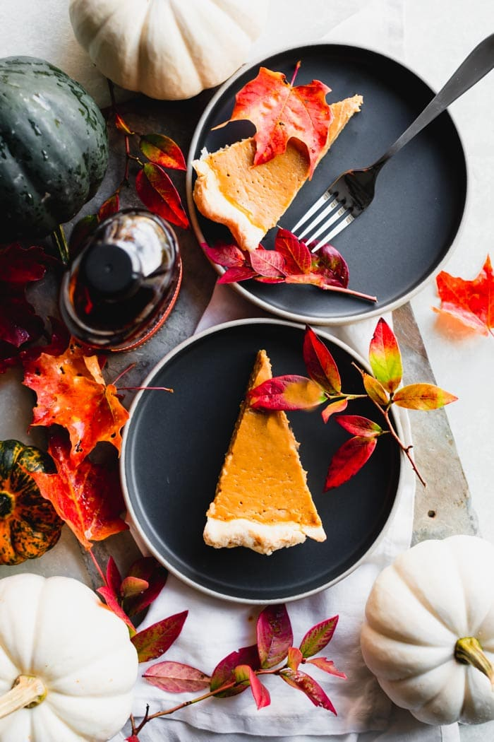 two plates of pie with gourds, a bottle of bourbon and fall leaves