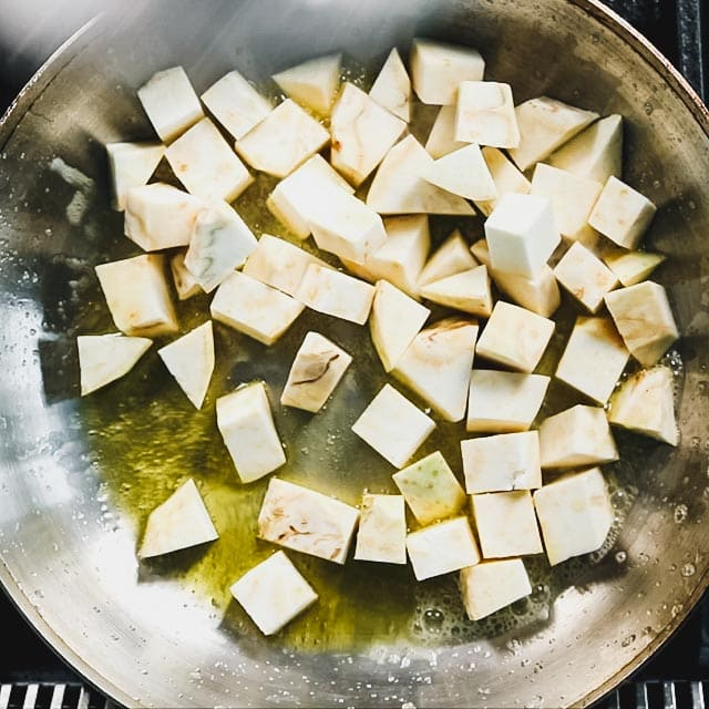 Melt the butter in a large skillet. Add olive oil and swirl to combine. Add the celery root and cook, stirring occasionally until it is browned in spots.