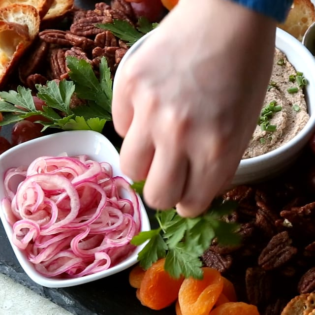adding parsley to the charcuterie board