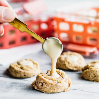 A close up of pouring the maple cream into the center of the cookie