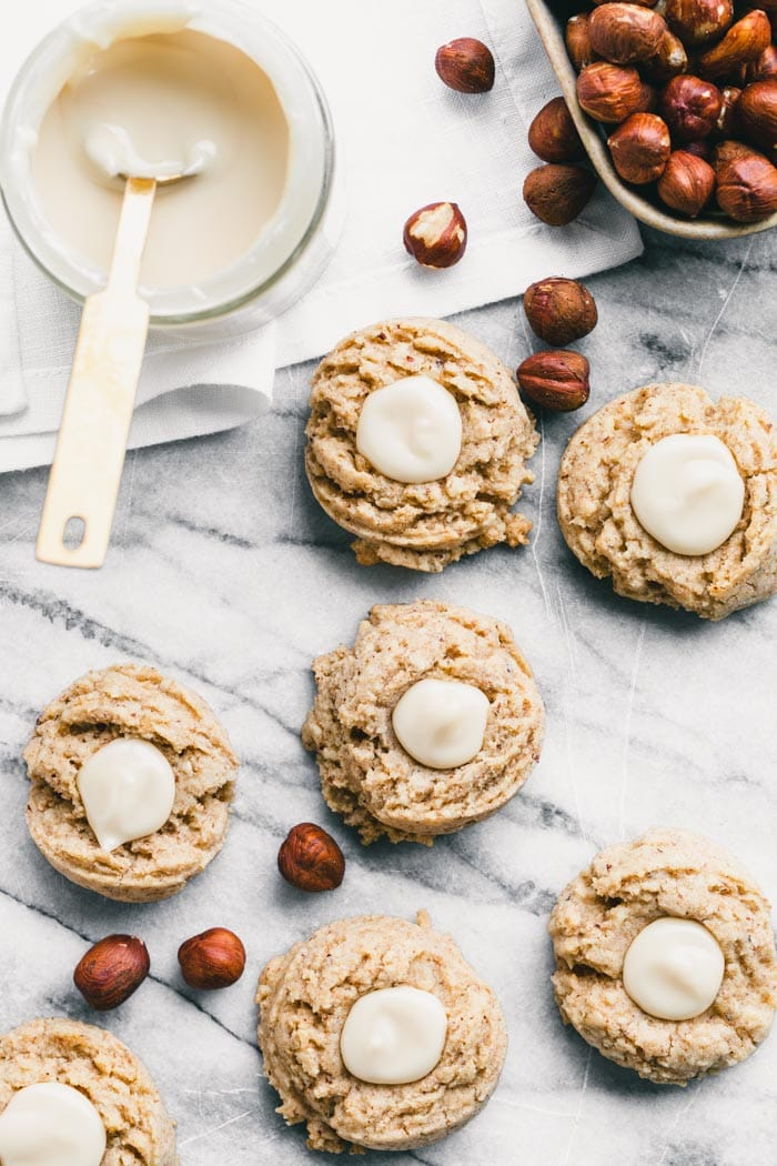 work surface with cookies, hazelnuts and maple cream