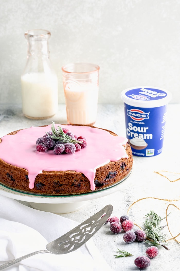 Cranberry cake and a container of FAGE sour cream on a white table
