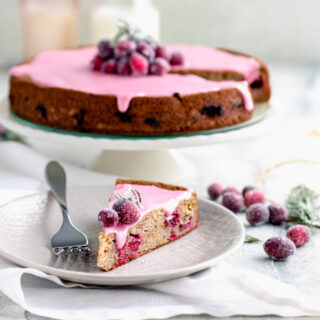 cranberry cake from the side and a slice on the plate