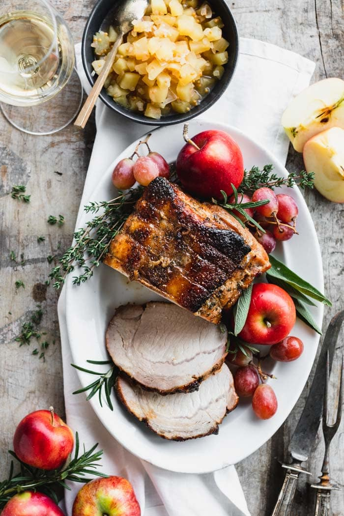 Roasted Pork Loin with apples and herbs on an oval platter from overhead