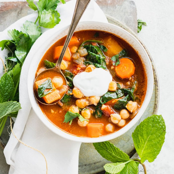 a closeup of a bowl of chickpea stew with a dollop of yogurt on top