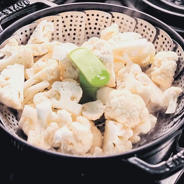 the cauliflower in the steamer basket