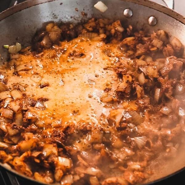 adding beer to the skillet to deglaze the pan