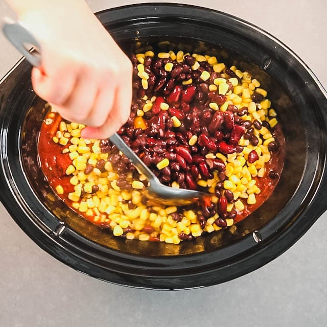 When there is one hour left, stir in beans and corn