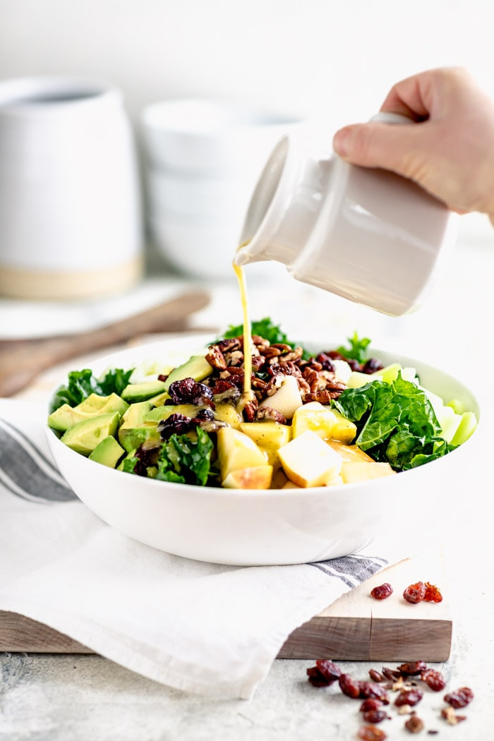 a white bowl with kale salad, a pitcher of dressing is being poured over it