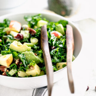 A bowl of tossed kale salad